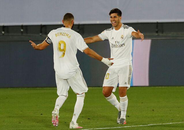 ماركو أسينسيو لاعب ريال مدريد يحتفل بتسجيل هدفه الثاني مع كريم بنزيما في  الدوري الإسباني.