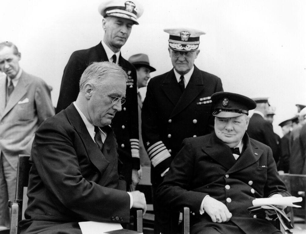 الرئيس الأمريكي فرانكلين روزفلت ورئيس الوزراء البريطاني ونستون تشرشل يجتمعان على متن السفينة الحربية البريطانية إتش إم إس أمير ويلز خلال المؤتمر الأطلسي لمدة خمسة أيام في القاعدة البحرية العسكرية أرجنتينيا باي، قبالة نيوفاوندلاند، كندا ، في 10 أغسطس/ آب 1941.  يستمعون خلفهم (من اليسار) الأدميرال إي. كينغ، قائد الأسطول الأطلسي البحري الأمريكي والأدميرال هارولد ر. ستارك، رئيس العمليات البحرية الأمريكية.