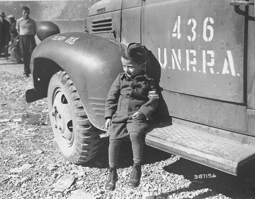 جوزيف شليفشتاين، أربعة أعوام، أحد الناجين من لمعسكر التركيز النازي بوتشينوالد، يسند على سيارة تابعة لمنظمة إدارة الأمم المتحدة للإغاثة والتأهيل (أونرا) بعد تحرير المخيم بقليل، عام 1945