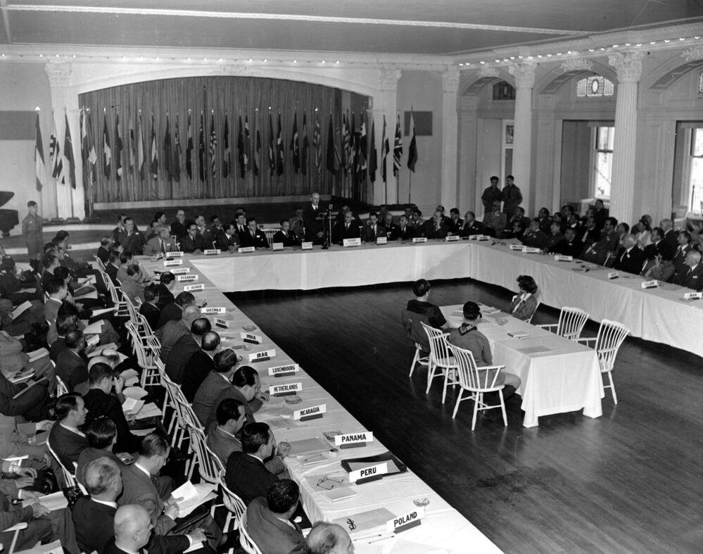 نظرة عامة لجلسة عامة لمؤتمر الأمم المتحدة النقدي في بريتون وودز، نيو هامبشاير. 4 يوليو/ تموز عام 1944. حيث حضره مندوبون من 44 دولة. السناتور تشارلز توبي، هو المتحدث وسط الصورة.