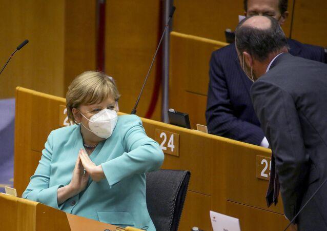 أرشيف من 8 يوليو 2020، ترحب المستشارة الألمانية أنجيلا ميركل بالحضور بكوعها أثناء جلسة عامة في البرلمان الأوروبي في بروكسل.