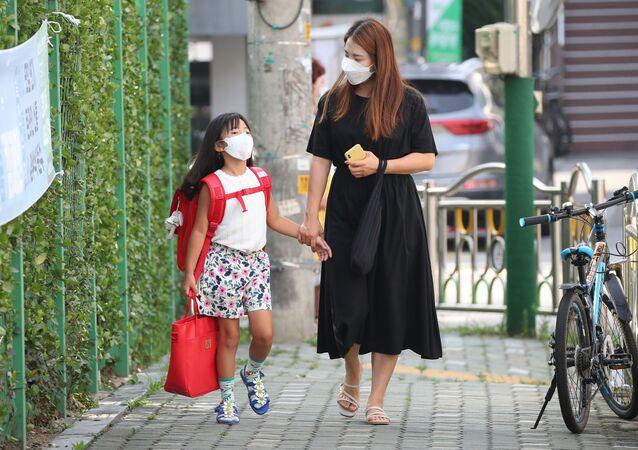 أم تقوم بتوصيل ابنتها إلى المدرسة في سئول، في إطار الاجراءات الاحترازية لمنع تفشي فيروس كورونا، كوريا الجنوبية 25 أغسطس 2020