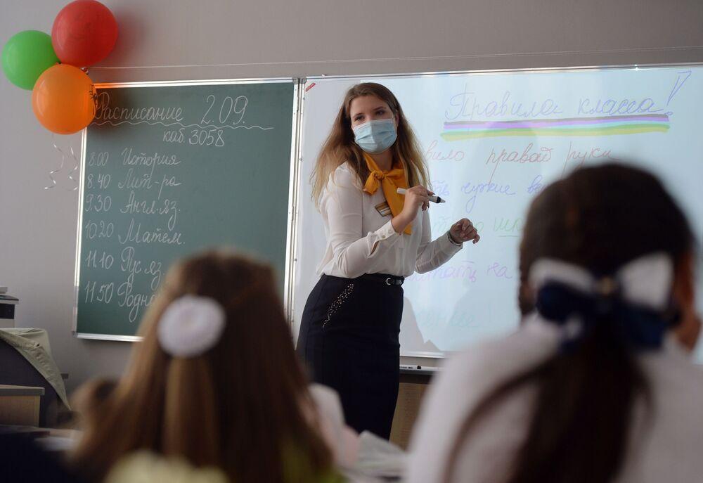 مدرّسة إبتدائي تقوم بشرح التعليمات والإرشادات الجديدة بخصوص الاجراءات الصحية في مدرسة بمدينة يكاتيرينبورغ، روسيا1 سبتمبر 2020