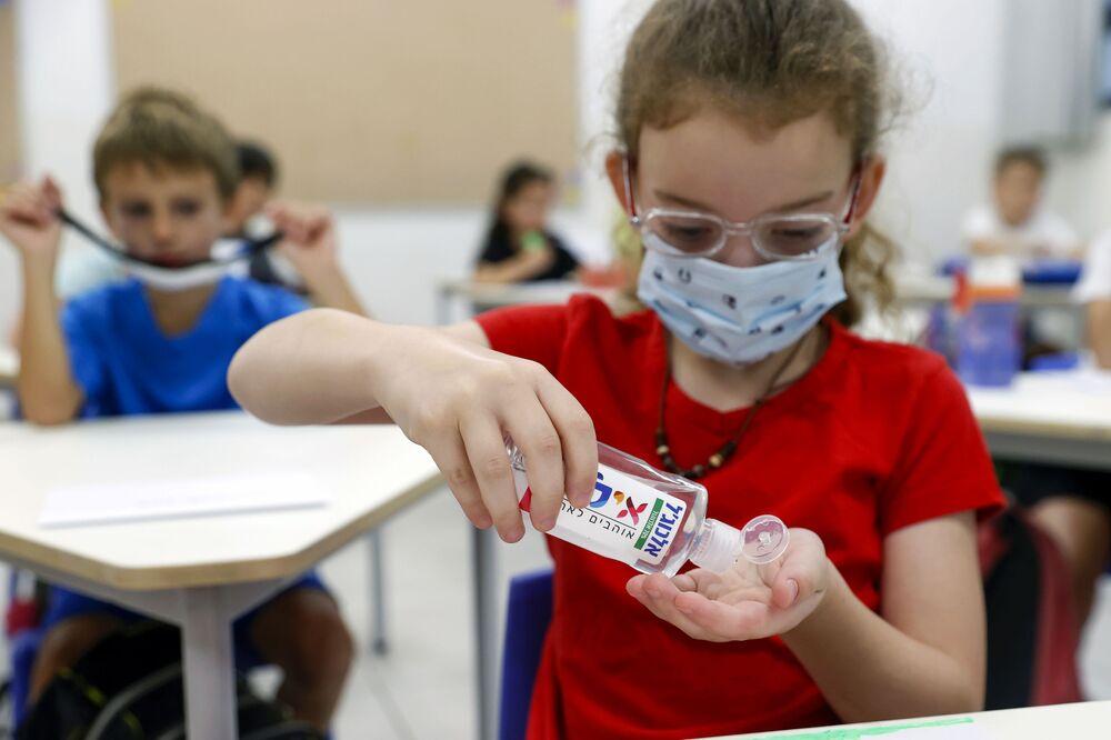 تلميذة تقوم بتعقيم يديها بالمطهر في الفصل في مدرسة في تل-أبيب، إسرائيل 1 سبتمبر 2020