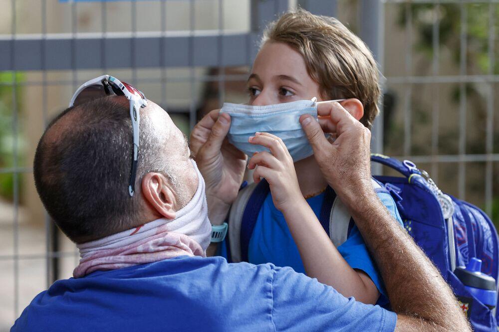 أب يضع كمامة طبية لابنه قبل دخول المدرسة في اليوم الأول من العام الدراسي في مدينة تل-أبيب، إسرائيل 1 سبتمبر 2020