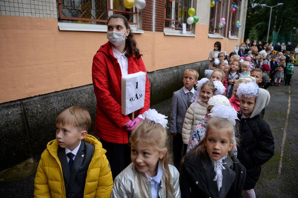 تلاميذ مردسة ابتدائية يتوجهون إلى فصولهم الدراسية برفة مدرستهم التي ترتدي كمامة طبية في مدينة سان بطرسبورغ، روسيا1 سبتمبر 2020