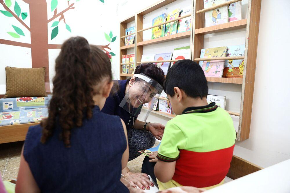 مدرّسة ترتدي قناع طبي وتتحدث إلى تلاميذها أثناء الفصل الدراسي،بعد رفع القيود المشددة في القدس 1 سبتمبر 2020
