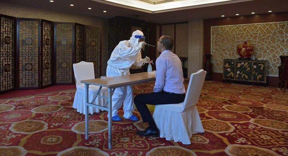 موظف يقوم بعمل اختبار لأحد المشاركين في مراسم تكريم الأطباء والمتطوعين (قبل بدء الحفل) في مكافحة تفشي فيروس كورونا (كوفيد-19)، في قاعة الشعب الكبرى في بكين، 8 سبتمبر 2020