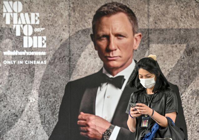 إمرأة ترتدي كمامة طبية للوقاية من فيروس كورونا المستجد وتقف أمام ملصق فيلم العميل السري البريطاني جيمس بوند No Time to Die