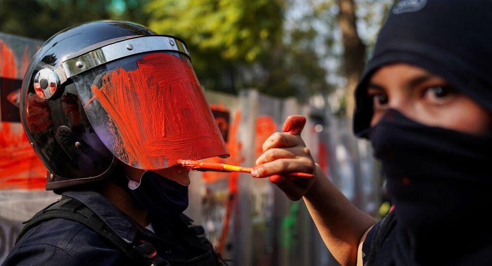 عضوة في مجموعة نسوية ترسم على خوذة ضابط شرطة لمكافحة الشغب خلال احتجاج ضد العنف الجنسي وعنف الشرطة، في مكسيكو سيتي، المكسيك، 11 نوفمبر 2020.