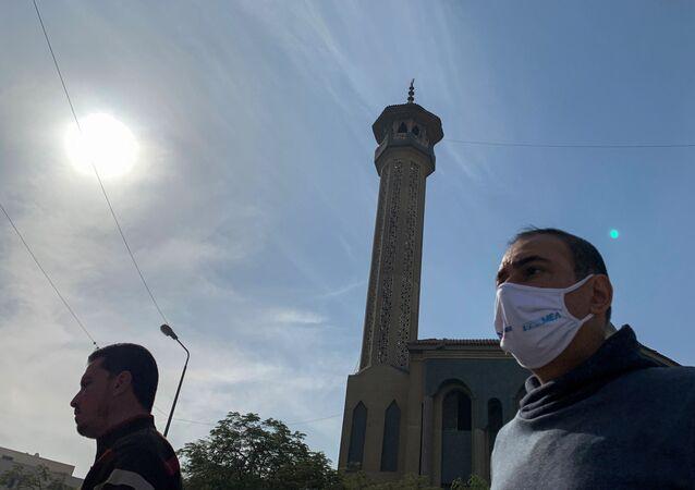 رجل يرتدي كمامة واقية من فيروس كورونا وفي الخلفية مأذنة مسجد في مصر نوفمبر تشرين الثاني