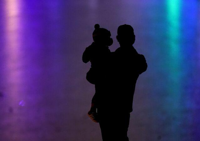 رجل يحمل طفل ويرتديان كمامات واقية من فيروس كورونا المستجد 26 ديسمبر 2020  كانساس