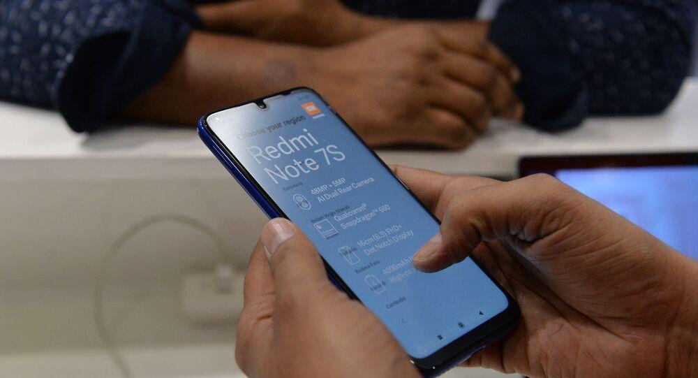 مستهلك بتفقد هاتف شاومي في أحد متاجرها بالهند