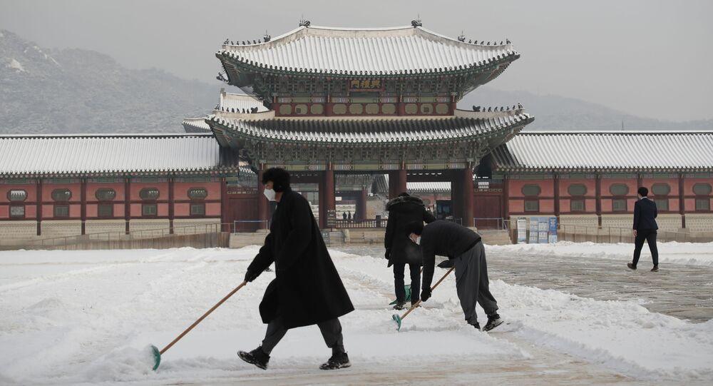 أشخاص يرتدون كمامات كإجراء احترازي ضد فيروس كورونا يقومون بإزالة الثلوج في قصر غيونغبوك، أحد المعالم المعروفة في كوريا الجنوبية، في سيئول، 13 يناير 2021.