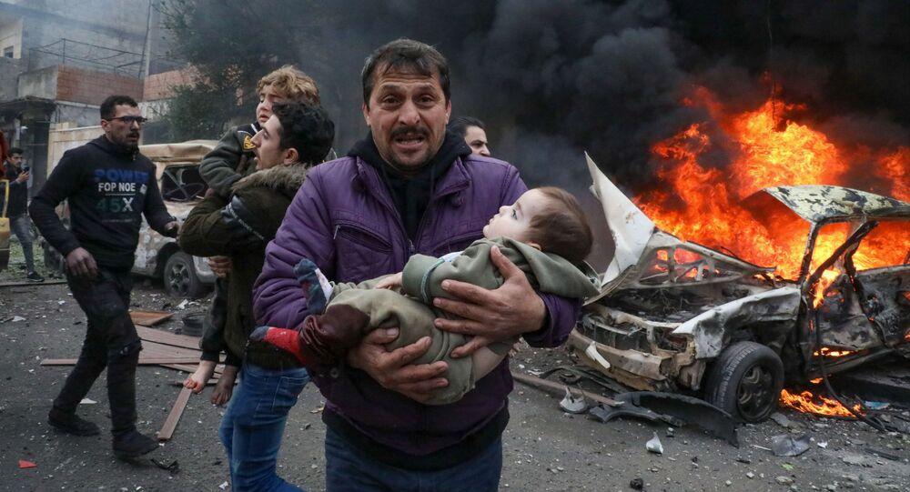 تحذير محتوى حساس - مدني يحمل ضحية صغيرة في موقع انفجار سيارة مفخخة ببلدة أعزاز بريف حلب الشمالي، سوريا 31  يناير2021