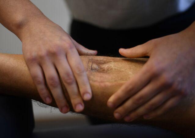 ساق شخص مريض يتم معالجته عن طريق التدليك