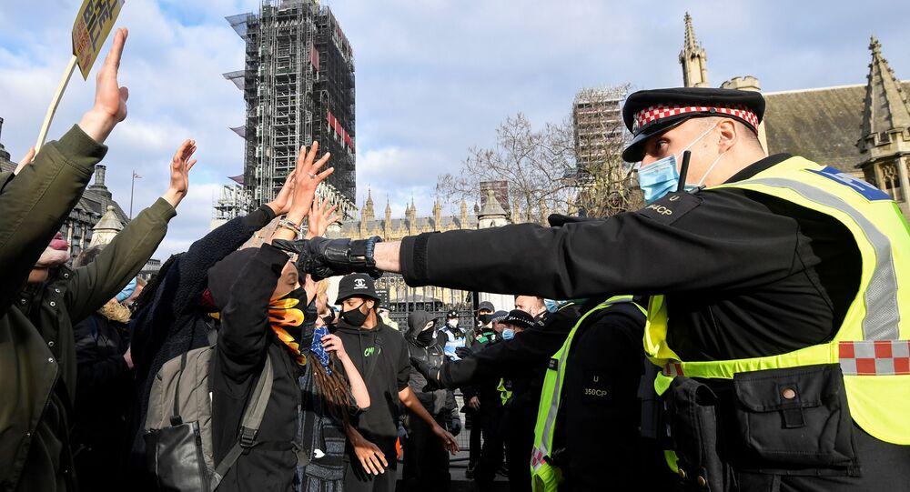 متظاهرون يرفعون أيديهم في وجوه ضباط الشرطة البريطانية خلال مظاهرة في لندن، بريطانيا، 3 أبريل / نيسان 2021