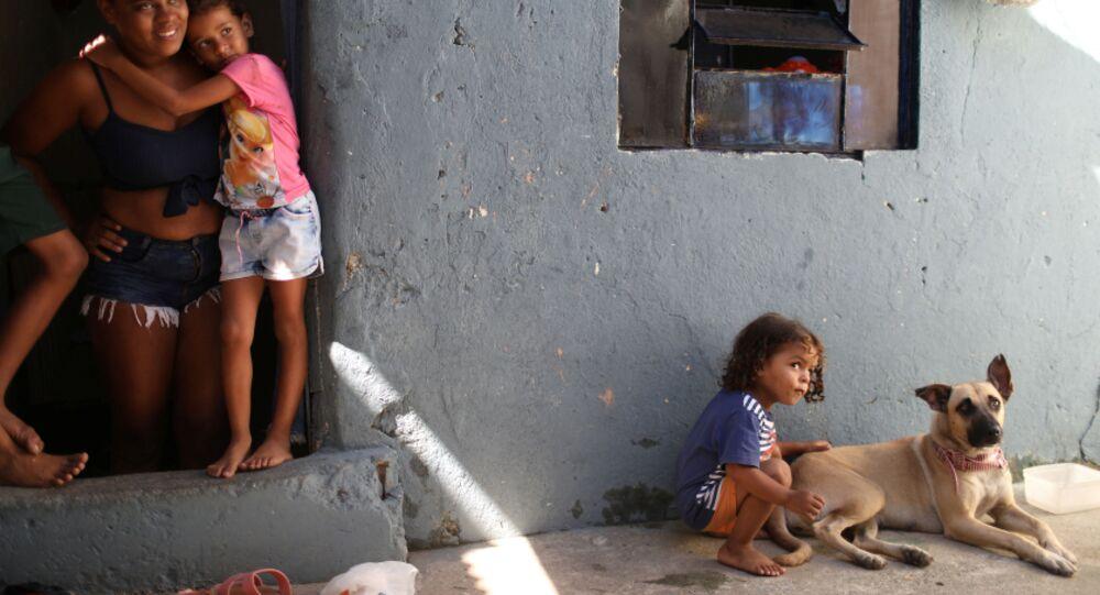 مونيك فيرناندا دي أسيس، 26 عامًا، تقف عند باب منزلها مع ابنتها إستير، حيث يلعب ابنها ميغيل مع كلبهم، بعد تلقي الطعام المتبرع به من مشروع Uma Mao Lava a Outra (يد واحدة تغسل الأخرى) خلال جائحة كورونا (كوفيد-19) في نيلوبوليس، ولاية ريو دي جانيرو، البرازيل، 6 أبريل 2021