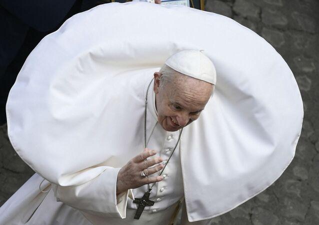 رياح ترفع من رداء البابا فرانسيس خلال اجتماعه العام الأسبوعي في الهواء الطلق مع الجمهور في ساحة سان داماسو بالفاتيكان، 19 مايو 2021