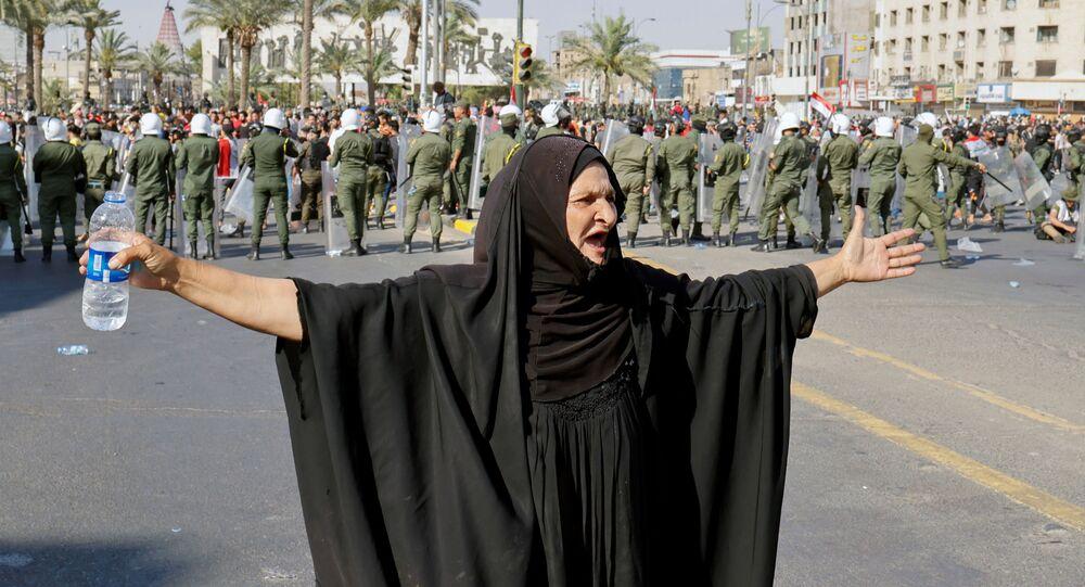 امرأة تشير إلى متظاهرين يشاركون في مظاهرة مناهضة للحكومة في بغداد، العراق، 25 مايو 2021