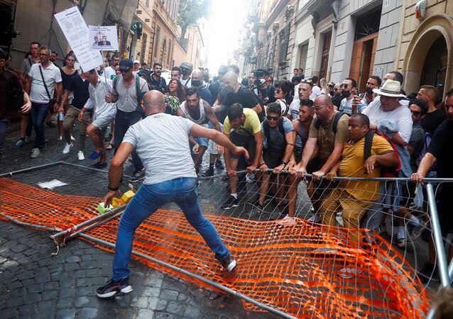 متظاهرون يزيلون حاجزًا للشرطة خلال مظاهرة ضد خطة الممر الأخضر في روما، إيطاليا 27 يوليو 2021