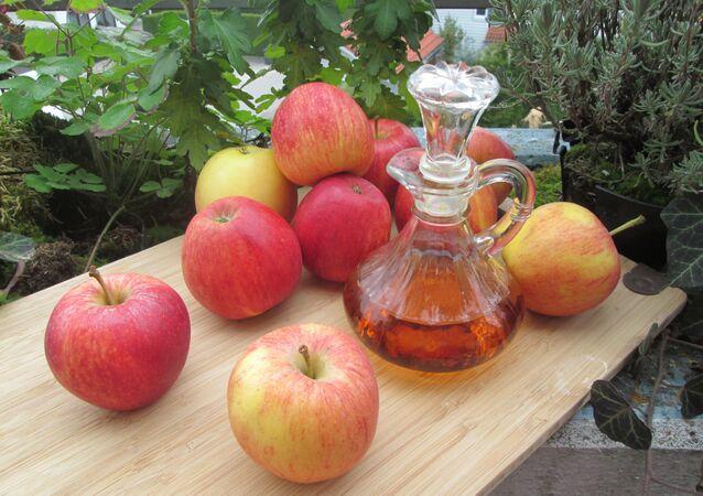 عصير خل التفاح إلى جانب فاكهة التفاح الشهية