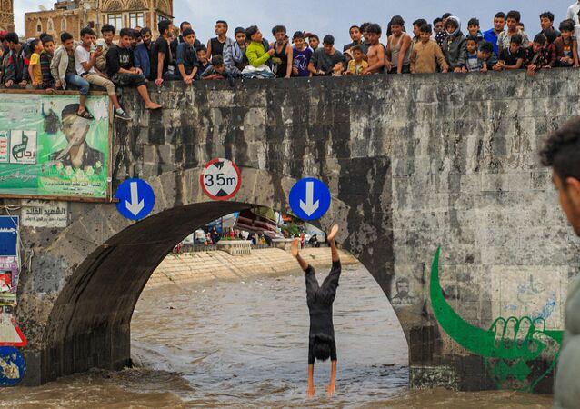 شبان يشاهدون أحدهم يقفز من جسر عبر قناة تصريف غمرتها المياه بعد هطول أمطار غزيرة في المدينة القديمة صنعاء، اليمن في 3 أغسطس 2021