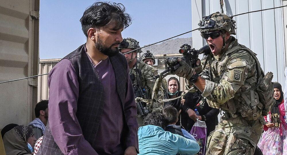جندي أمريكي في مطار كابول يوجه سلاحه نحو أفغاني يحاول مغادرة البلاد إثر سيطرة طالبان على الحكم في أفغانستان
