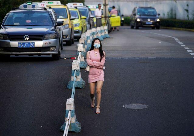 امرأة ترتدي قناعًا واقيًا تمشي في أحد الشوارع، بعد الإعلان عن حالات الإصابة جديدة بمرض فيروس كورونا (كوفيد-19) في شنغهاي، الصين  23 أغسطس 2021