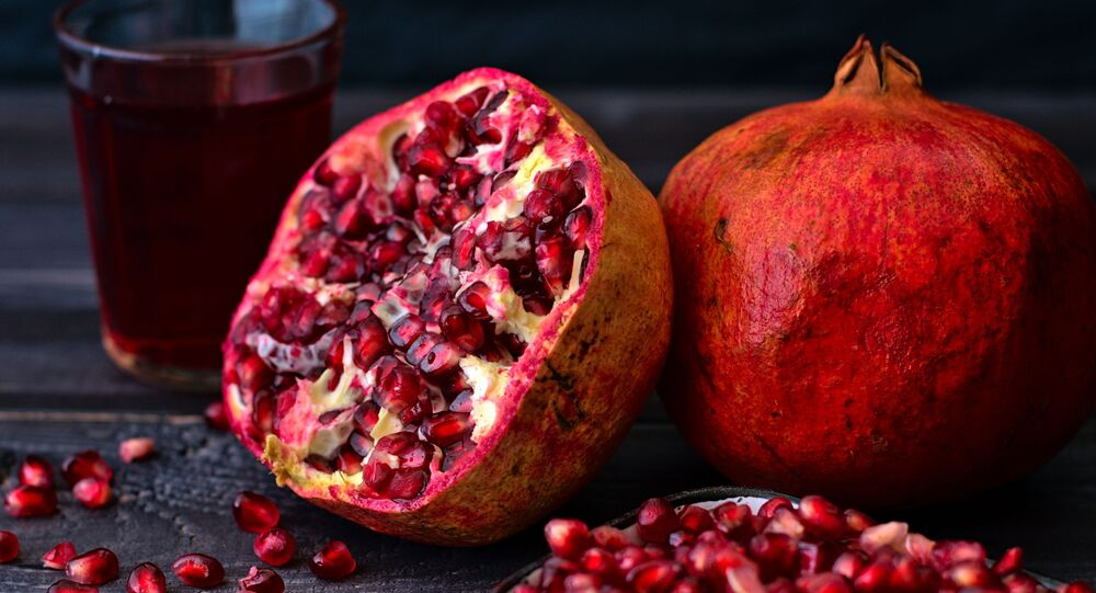 فاكهة الرمان وكأس من عصير الرمان