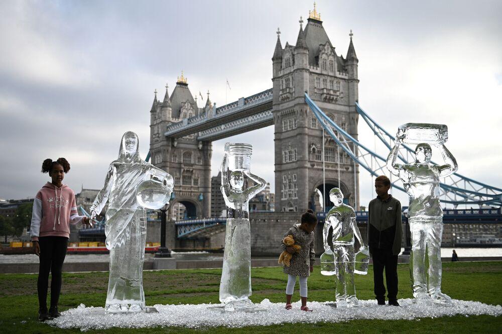 أطفال يقفون أمام منحوتات جليدية تصور أشخاصًا يجمعون المياه من قبل منظمة Water Aid الخيرية، لإظهار هشاشة المياه والتهديد الذي يشكله تغير المناخ، لندن، إنجلترا 15 سبتمبر 2021.