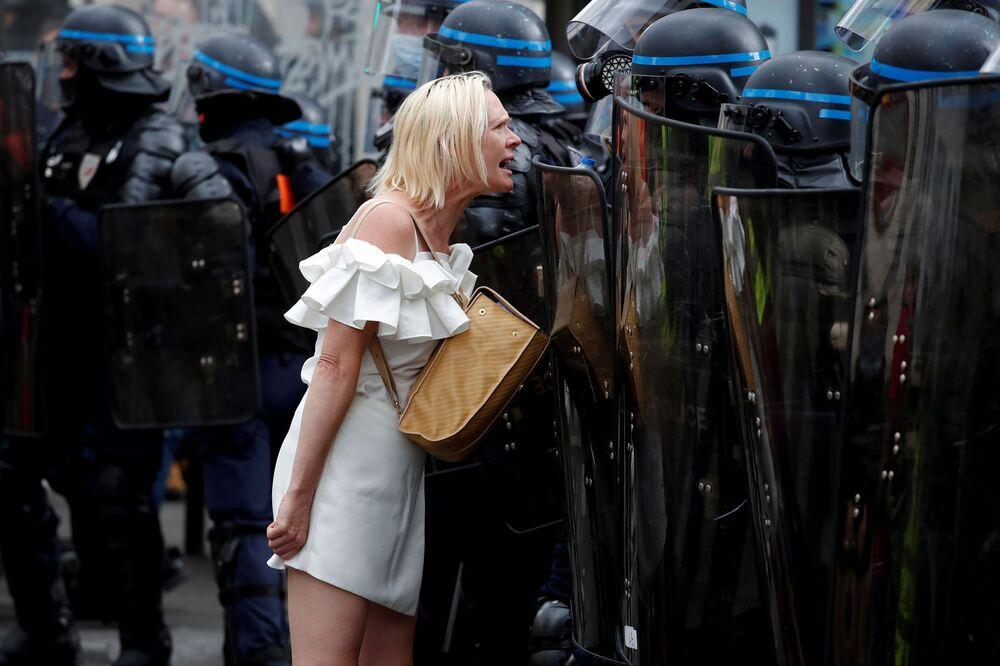 متظاهرة يواجه ضباط شرطة مكافحة الشغب خلال مظاهرة ضد قيود فرنسا  بما في ذلك التصاريح الصحية الإلزامية، لمكافحة جائحة فيروس كورونا (كوفيد-19) في باريس، فرنسا، 11 سبتمبر 2021