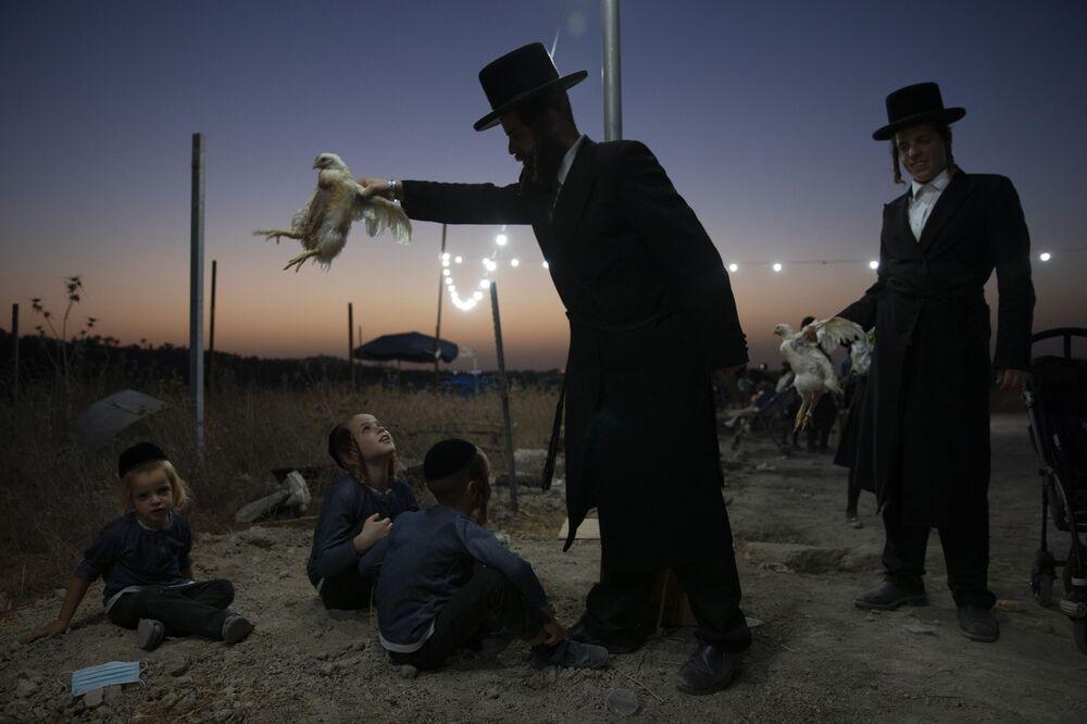 رجل دين يهودي يمسك بدجاجة فوق أطفاله كجزء من طقوس كاباروت في بيت شيمش، إسرائيل، 13 سبتمبر  2021.