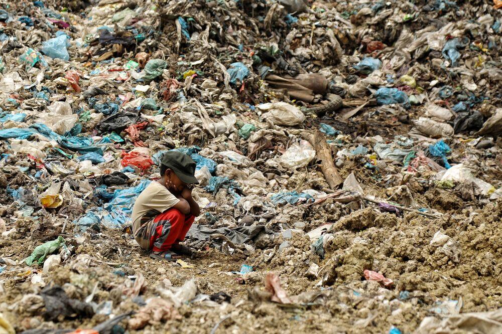 ابن جامع القمامة يستريح بينما يبحث والده (ليس في الصورة) عن المواد التي يمكن إعادة بيعها، في موقع مكب النفايات في أليو لييم، في لهوكسيوماوي، إندونيسيا 15 سبتمبر 2021.