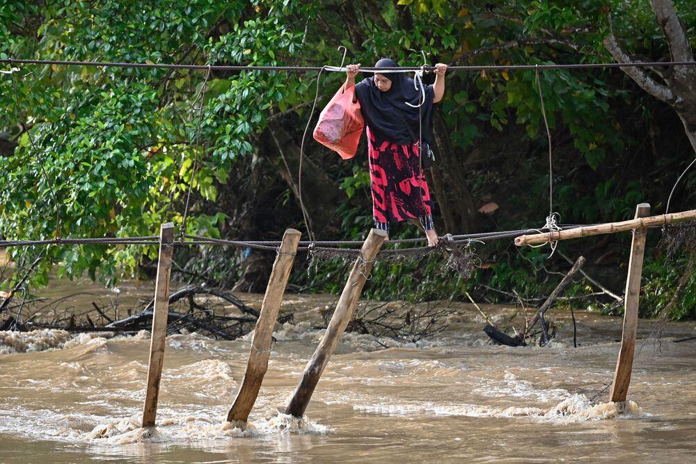 امرأة تعبر نهرًا باستخدام بقايا جسر جرفته المياه أثناء الفيضانات في العام السابق، في قرية ماليلا في لوو ريجنسي، جنوب سولاويزي، 13 سبتمبر 2021.