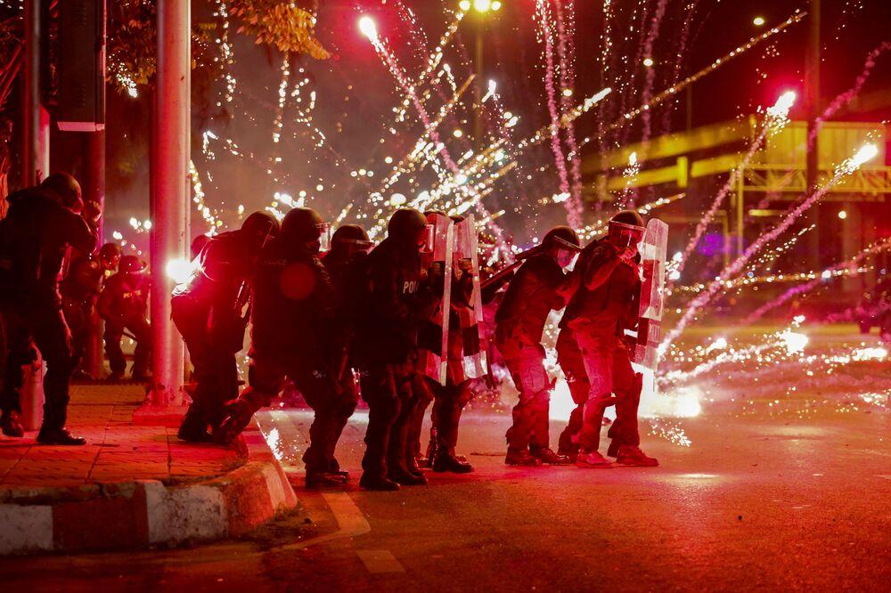 الألعاب النارية التي ألقاها متظاهرون تنفجر أمام صف من ضباط شرطة مكافحة الشغب خلال مظاهرة مناهضة للحكومة في بانكوك، تايلاند، 13 سبتمبر 2021.