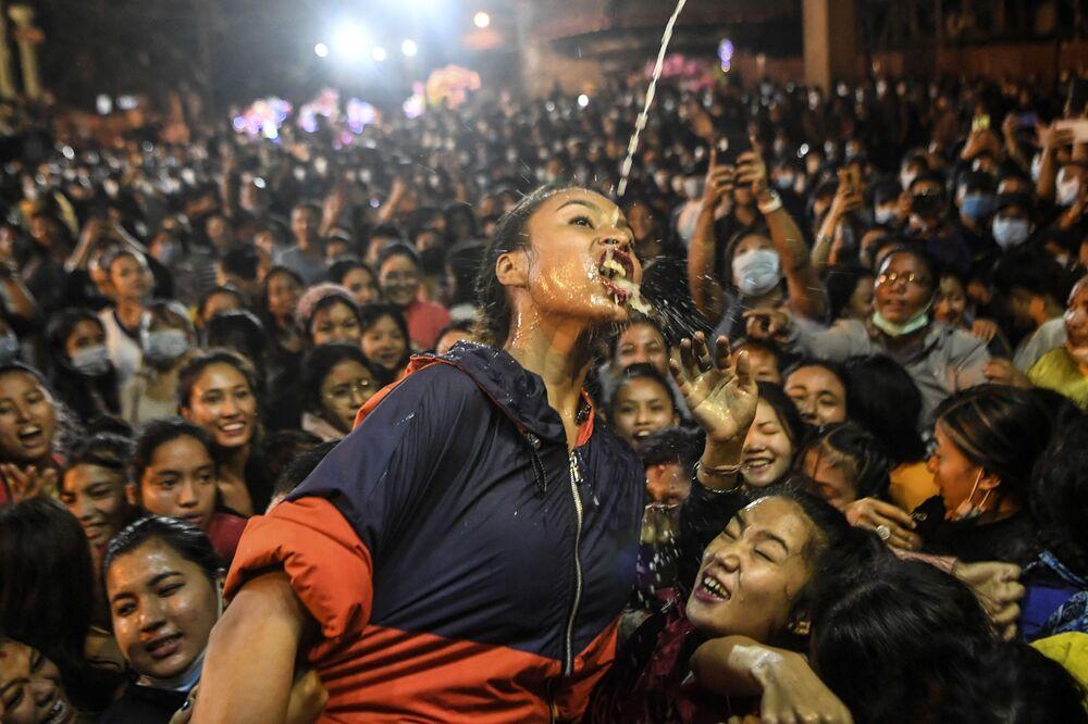 مخلصون يشربون النبيذ من تمثال شويت بهاراف (إله الحماية) خلال مهرجان إندرا جاترا في كاتماندو في 21 سبتمبر 2021.
