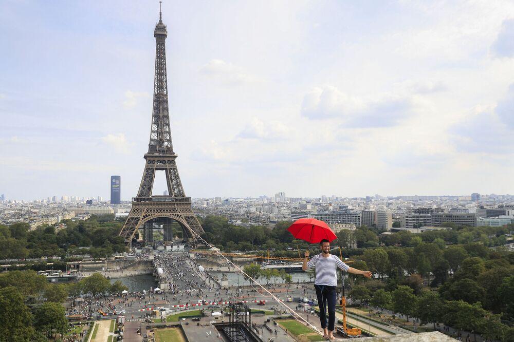 الفرنسي ناثان بولين يحمل مظلة وهو يسير، للمرة الثانية، على حبل مشدود بارتفاع 70 مترًا يمتد 670 مترًا بين برج إيفل ومسرح شايو الوطني، كجزء من أيام التراث الأوروبي الـ 38 وإطلاق الأولمبياد الثقافي في باريس، فرنسا 19 سبتمبر 2021.