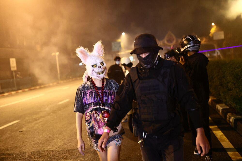 المتظاهرون المناهضون لحكومة بانكوك، أحدهم يرتدي رأس حيوان بينما يرتدي الآخر ملابس واقية، يسيران معًا بعد أن أطلقت الشرطة الغاز المسيل للدموع خلال مظاهرة للاحتفال بالذكرى السنوية الـ 15 منذ الانقلاب العسكري في البلاد في عام 2006، 19 سبتمبر 2021، حيث حثوا على استقالة الإدارة الحالية بسبب تعاملها مع أزمة فيروس كورونا.
