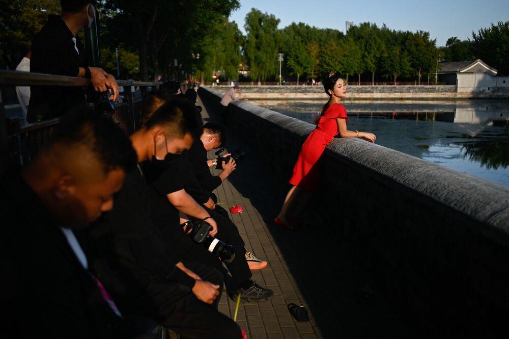 امرأة تقف لالتقاط صورة زفاف خارج المدينة المحرمة في بكين في 22 سبتمبر 2021.