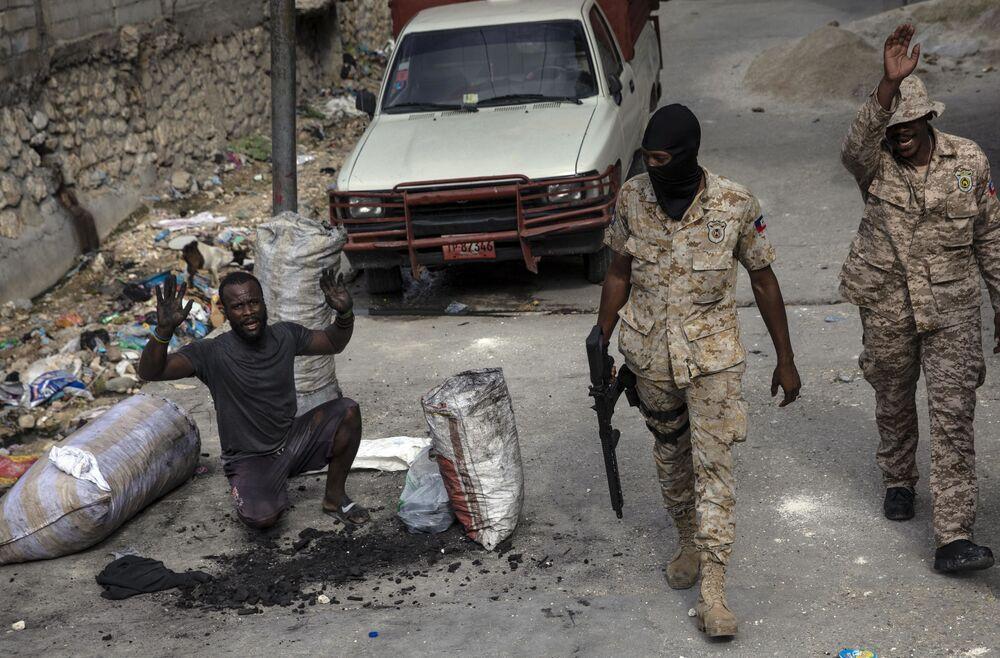 رجل يرفع ذراعيه لإظهار براءته بينما يقوم رجال الشرطة بدوريات في شوارع وسط مدينة بورت أو برنس، حيث أقام السكان حاجزًا احتجاجًا على اتهام الشرطة بقتل رجل أثناء مداهمة، هايتي  22 سبتمبر 2021.