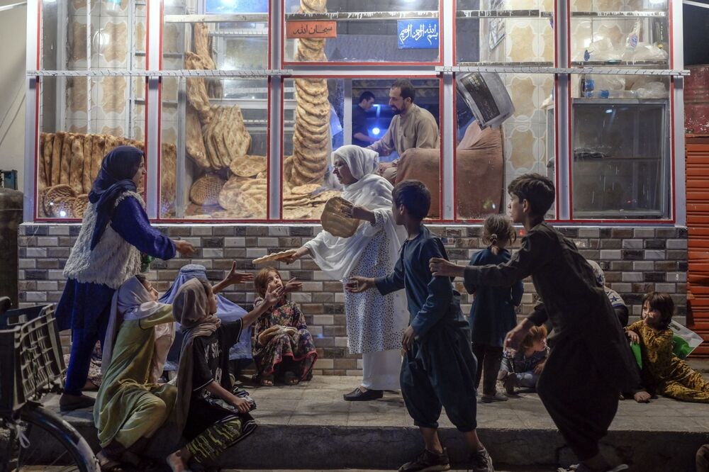 امرأة تقدم الخبز للأشخاص اليافعين المحتاجين أمام مخبز في كابول، أفغانستان 19 سبتمبر 2021.