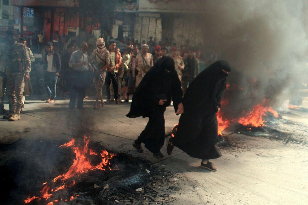 نساء يمرون بجوار إطارات محترقة خلال احتجاجات على تدهور الوضع الاقتصادي وانخفاض قيمة العملة المحلية في تعز، اليمن، 27 سبتمبر 2021.