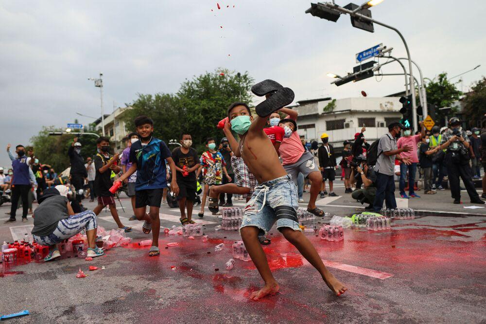 المتظاهرون الشباب المناهضون للحكومة يلقون زجاجات من الطلاء الأحمر على الشرطة خلال مظاهرة في بانكوك في 27 سبتمبر 2021، حيث دعا النشطاء إلى استقالة رئيس الوزراء التايلاندي برايوت تشان أو تشا بسبب تعامل الحكومة مع فيروس كورونا كوفيد-19.