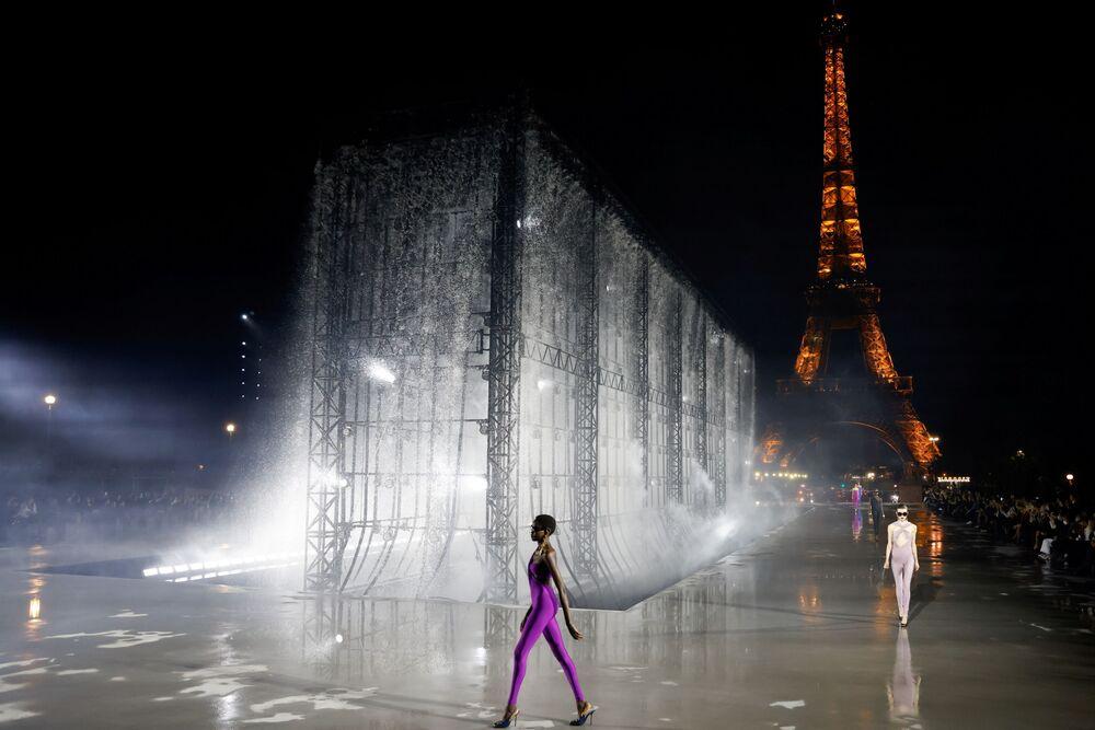عارضة أزياء تقدم تصاميم المصمم أنتوني فاكاريلو كجزء من عرض مجموعة الملابس الجاهزة النسائية لربيع /صيف 2022 لدار الأزياء سان لوران، أمام برج إيفل خلال أسبوع الموضة في باريس، فرنسا، 28 سبتمبر 2021.