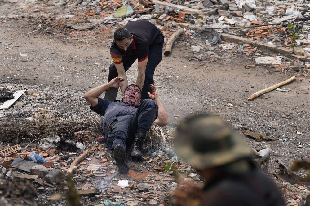 يأتي ضابط لمساعدة ضابط زميل أصيب في اشتباكات خلال احتجاج للسكان الأصليين ضد مشروع قانون مقترح يجرم غزو الأراضي، خارج الكونغرس في أسونسيون، باراغواي ، 29 سبتمبر 2021.