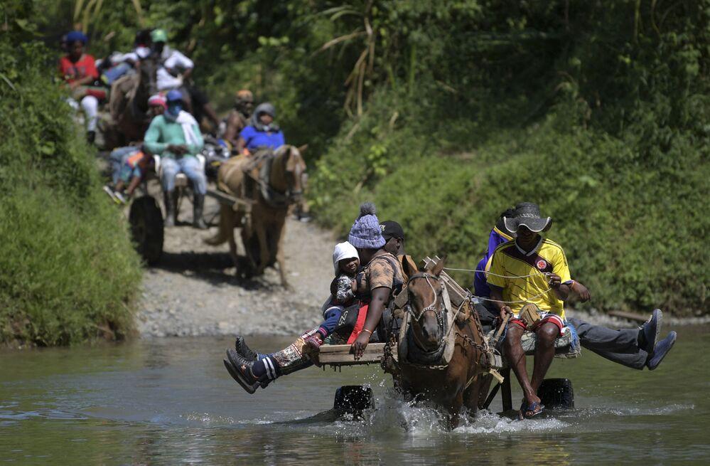 المهاجرون الهايتيون يعبرون النهر في عربات تجرها الخيول قبل التوجه إلى الحدود مع بنما في أكاندي، كولومبيا في 25 سبتمبر 2021.