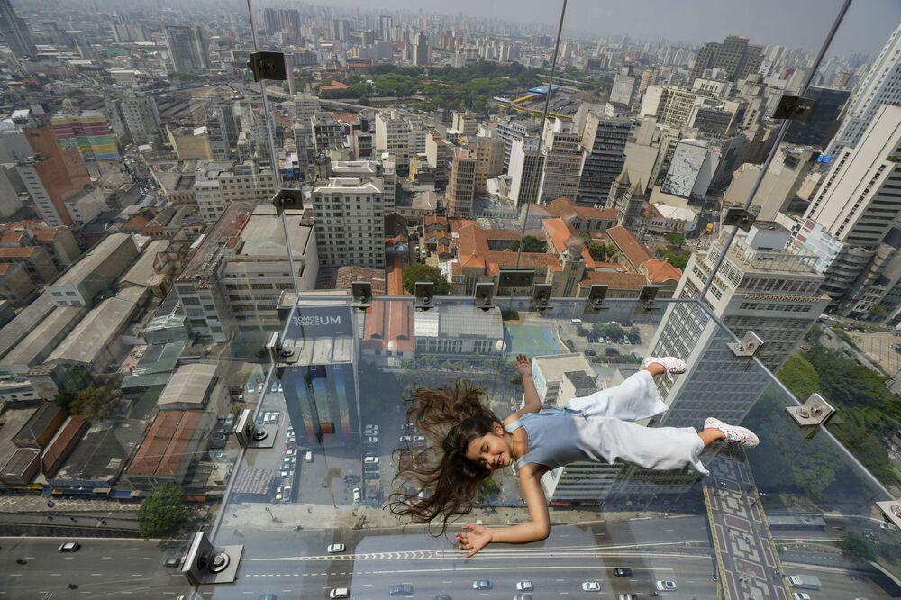 فتاة ترقد على أرضية زجاجية للمرصد سامبا سكاي في الطابق 42 من مبنى Mirante do Vale في وسط مدينة ساو باولو، البرازيل، 29 سبتمبر 2021.