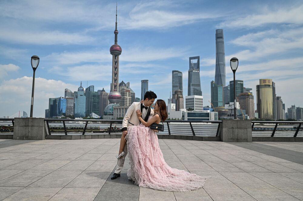 زوجان يقفان خلال جلسة تصوير قبل الزفاف على الكورنيش في بوند على طول نهر هوانغبو في شنغهاي، الصين 24 سبتمبر 2021.