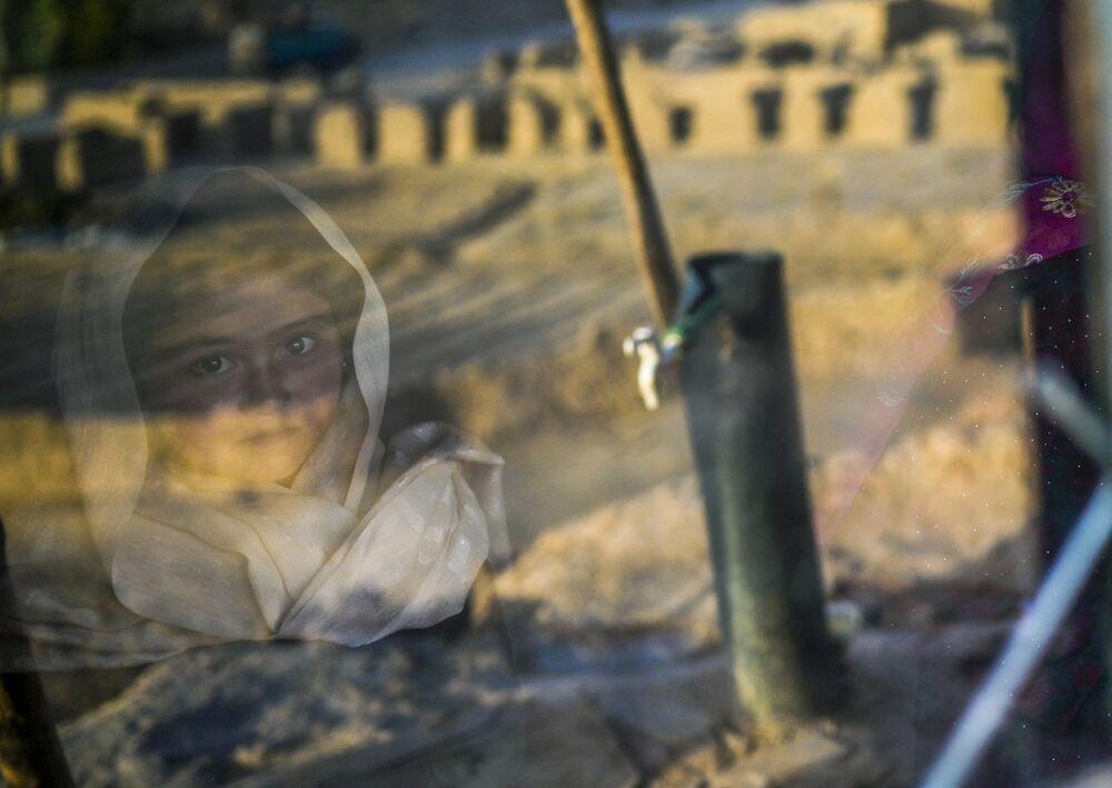 طفلة من هزارة تنظر من خلف زجاج بيتها الحجري في قرية باميان، أفغانستان 3 أكتوبر2021